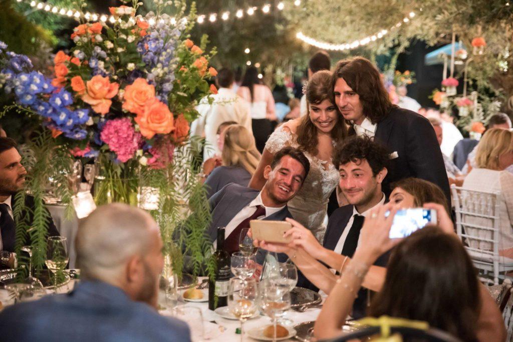 bruidspaar maakt praatje met gasten aan dinertafel in mooi gestylde tuin