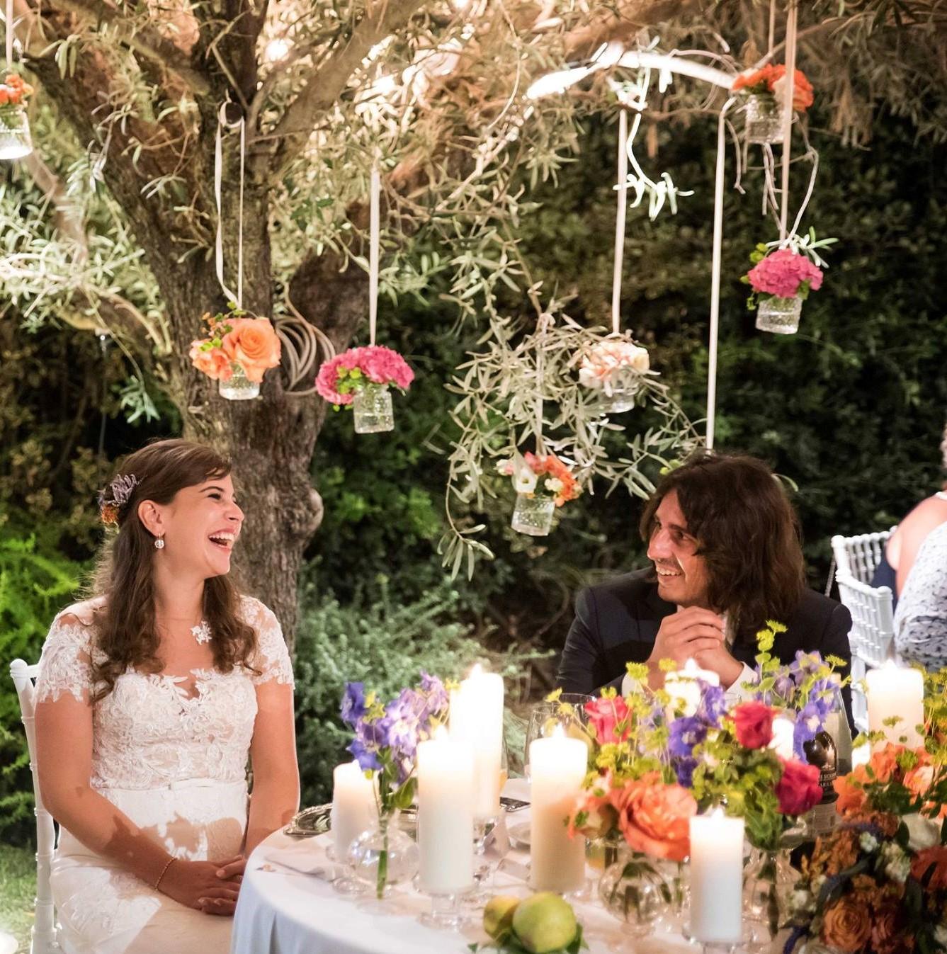 Bruidspaar aan dinertafel in prachtig gestylde tuin