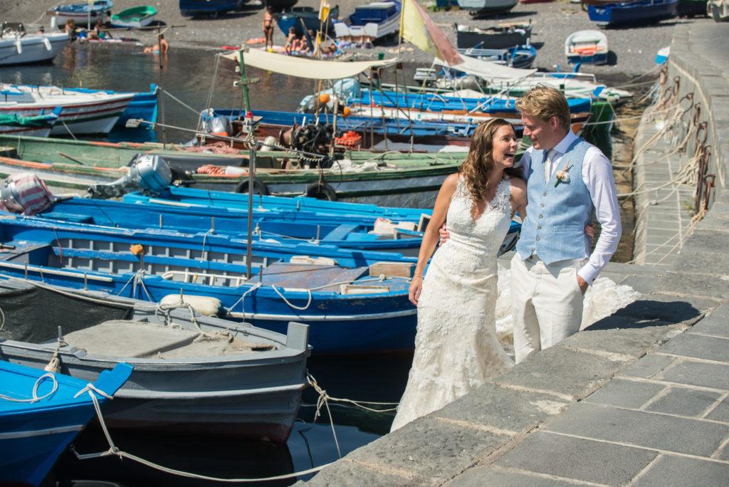 bruidspaar aan de waterkant met azuurblauwe vissersbootjes op de achtergrond Sicilië