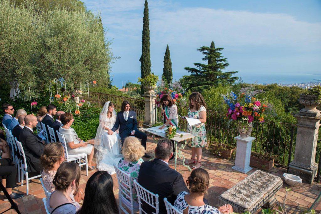 Bruidspaar tijdens ceremonie op terras met uitzicht  over zee en Catania