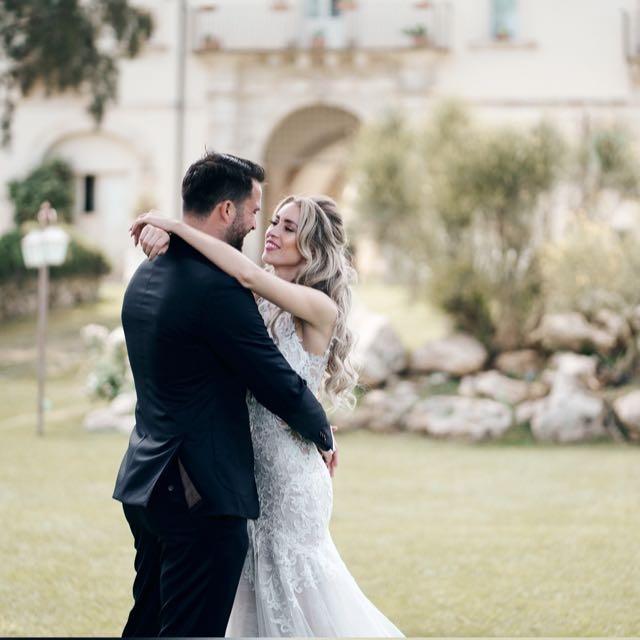 bruidspaar omarmt elkaar voor Castello Camemi in Sicilië