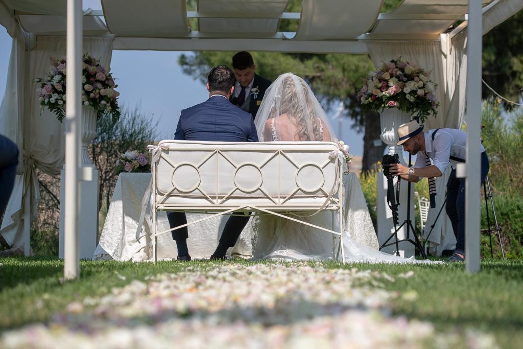 bruidspaar zittend op bruidsbankje tijdens trouwceremonie bij Castello Camemi Sicilië