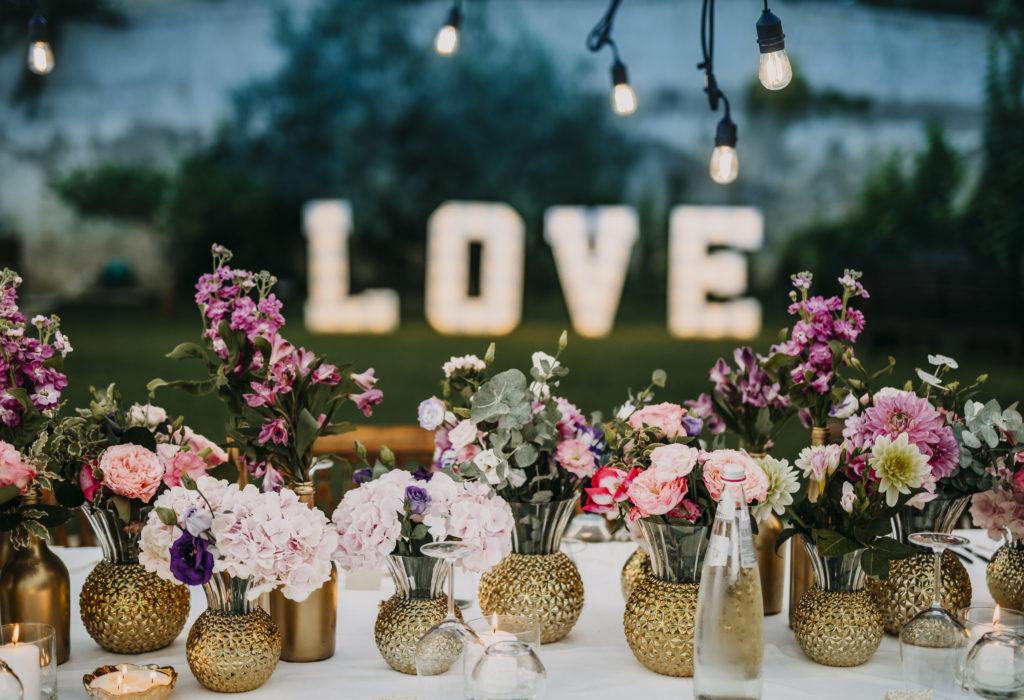 styling dinertafel huwelijk met goudkleurige vaasjes en roze/lila bloemen
