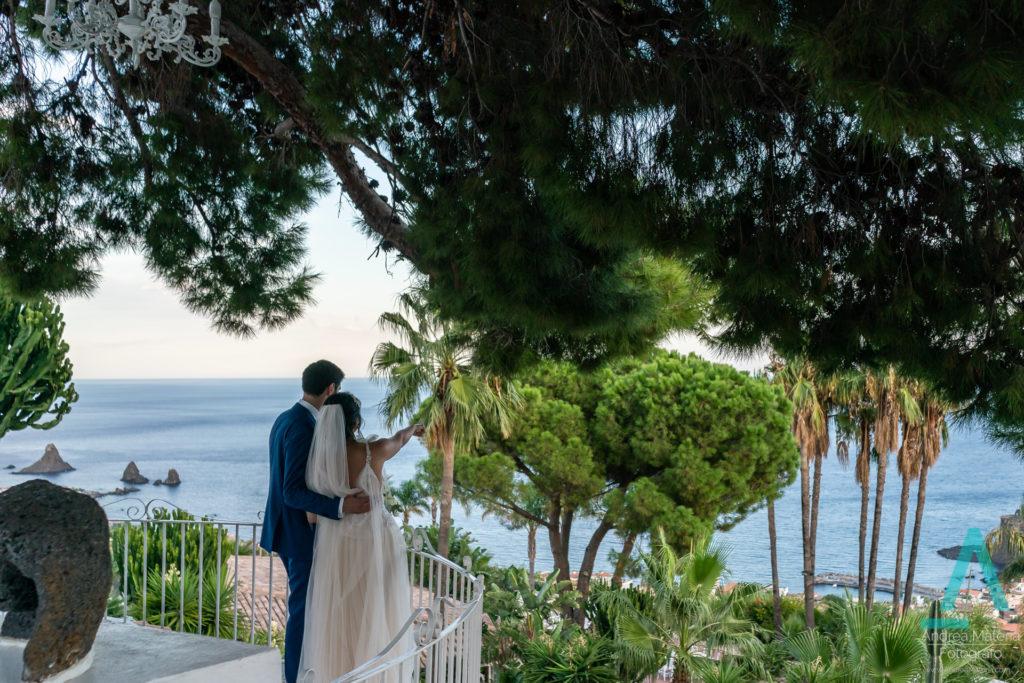 bruidspaar op terras bij Casa delle Terre Forti uitkijkend over de zee bij Aci Castello