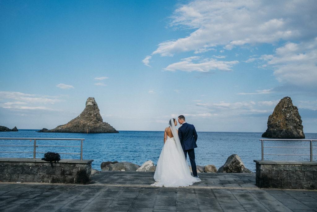 bruidspaar aan de zee in Aci Castello Sicilië