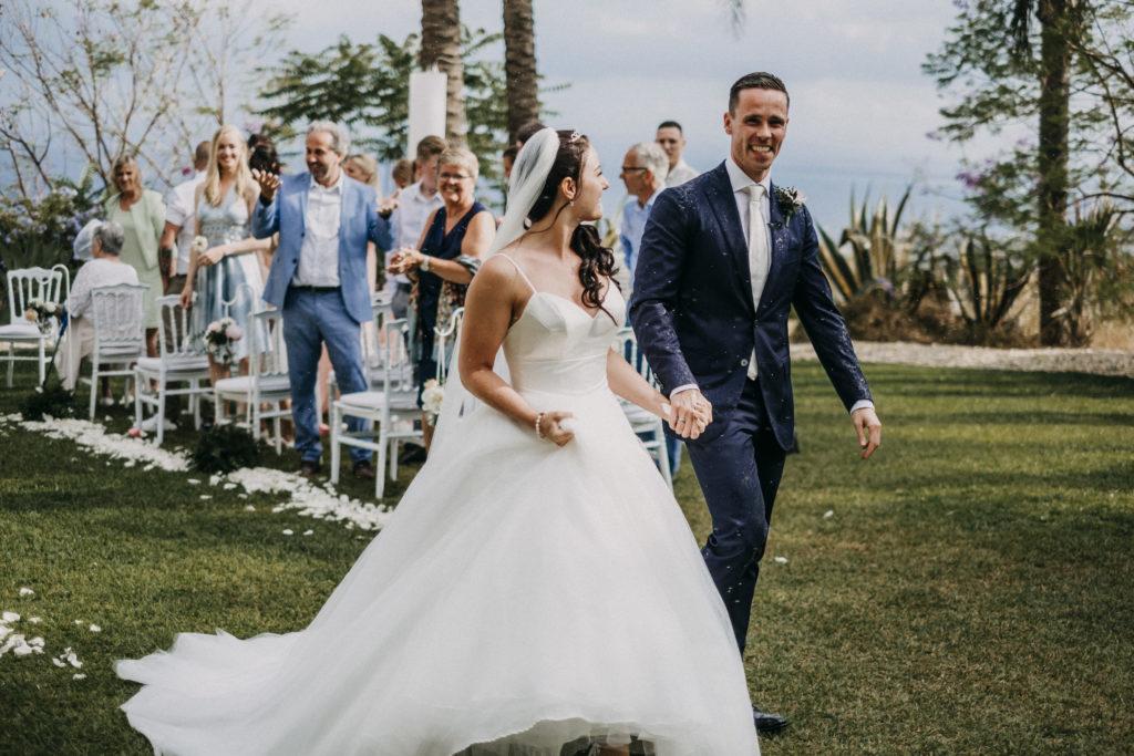 bruidspaar loopt door gangpad na de trouwceremonie