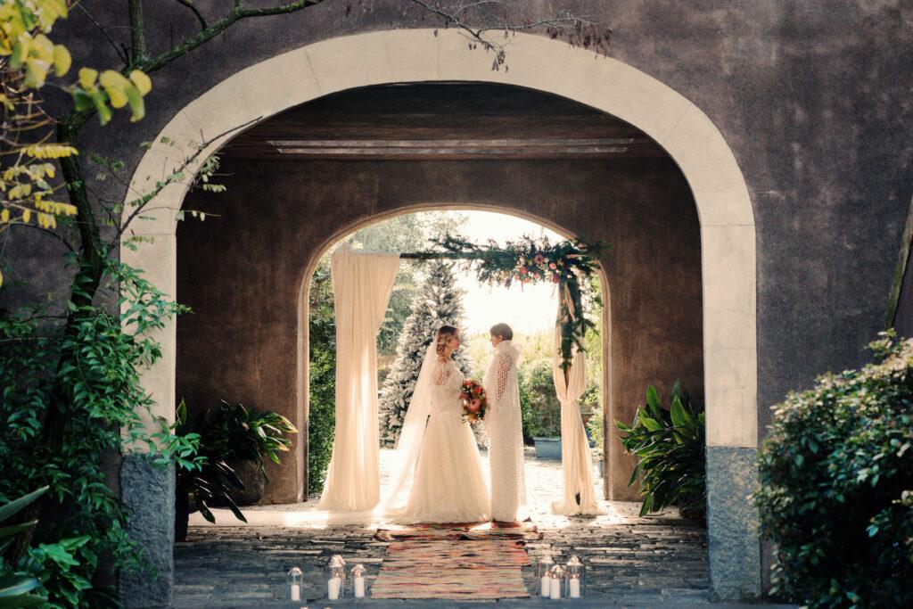 bruiden tijdens de trouwceremonie met bloemenboog en kerstboom op de achtergrond